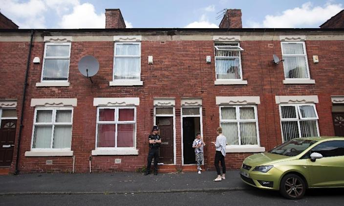 A police officer stands on duty outside the door of a raided residential property on Lindum Street in Moss Side, Manchester, on May 25, 2017 (AFP Photo/JON SUPER)