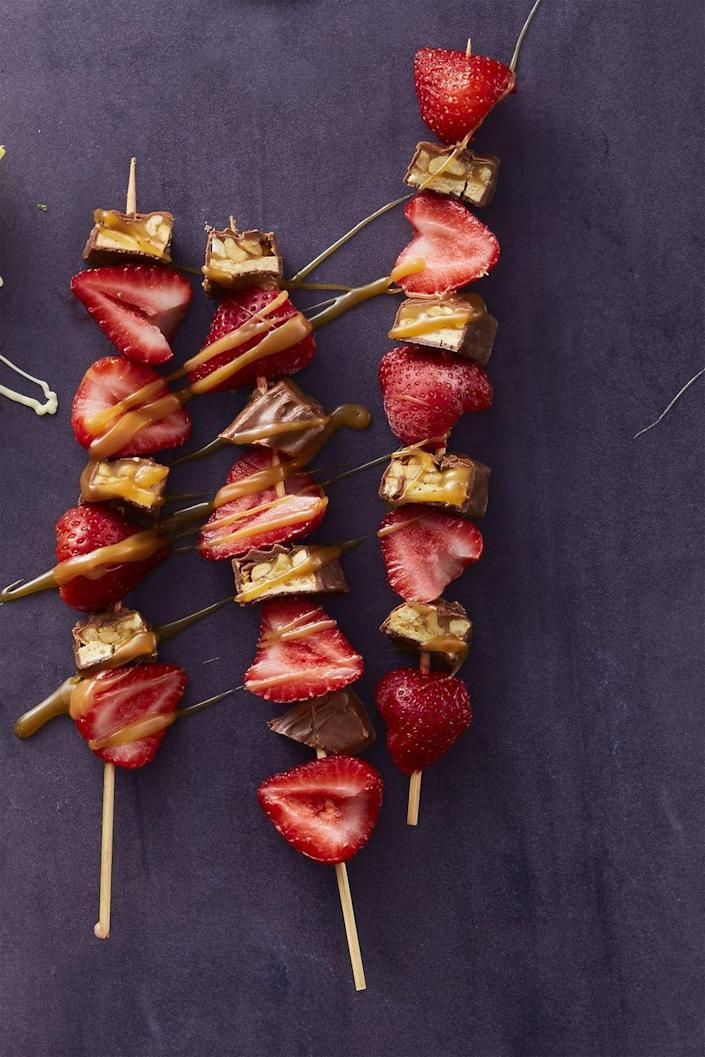 """<p>Sweet and savory come together in this delicious recipe. Simply cut up strawberries and Snickers bars and thread the pieces on kebab sticks.</p><p><em><strong><a href=""""https://www.womansday.com/food-recipes/food-drinks/recipes/a59413/strawberry-snickers-sticks-recipe/"""" rel=""""nofollow noopener"""" target=""""_blank"""" data-ylk=""""slk:Get the Strawberry and Snickers Sticks recipe."""" class=""""link rapid-noclick-resp"""">Get the Strawberry and Snickers Sticks recipe.</a></strong></em></p>"""