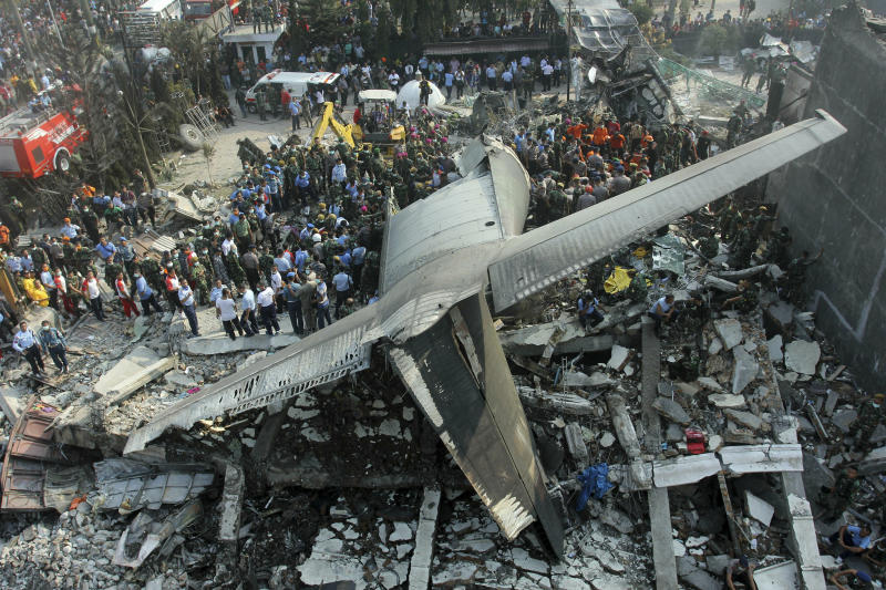 FILE - In this Tuesday, June 30, 2015 file photo, rescuers search for victims at the site where an Hercules C-130 air force cargo plane crashed into a residential neighborhood in Medan, North Sumatra, Indonesia. On Friday, March 15, 2018, The Associated Press has found that a similar photo from the Reuters news agency circulating on the internet was falsely identified as the Ethiopian Airlines Boeing 737 Max 8 jet that crashed on Sunday, March 10, 2019. (AP Photo/Yudha Lesmana)