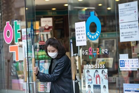 A person wearing a protective mask leaves a pharmacy in Seoul, South Korea. Photo: Bloomberg