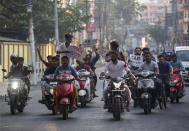 Indian protesters on motorbikes hold placards during a shutdown protest against the Citizenship Amendment Bill (CAB) in Gauhati, India, Tuesday, Dec. 10, 2019. Opponents of legislation that would grant Indian citizenship to non-Muslim illegal migrants from Pakistan, Bangladesh and Afghanistan have enforced an 11-hour shutdown across India's northeastern region. (AP Photo/Anupam Nath)