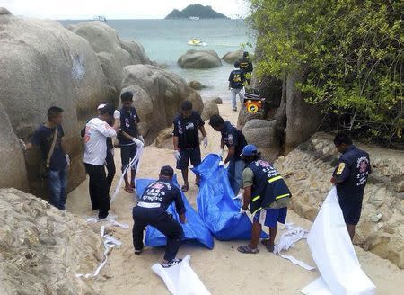 Rescue workers close bags with bodies of two foreign tourist found dead on a beach on Koh Tao island