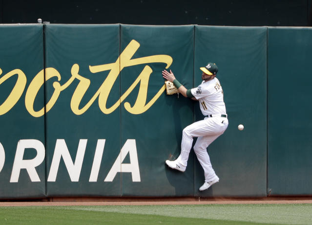 Oakland Athletics' Dustin Fowler crashes into the wall as he tries to catch a line drive double by Cleveland Indians' Francisco Lindor during the third inning of a baseball game Sunday, July 1, 2018, in Oakland, Calif. (AP Photo/Marcio Jose Sanchez)