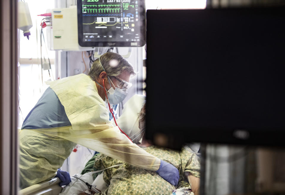 Dr. William Dittrich, M.D. looks over a COVID-19 patient in the Medical Intensive care unit (MICU) at St. Luke's Boise Medical Center in Boise, Idaho on Tuesday, Aug. 31, 2021. More then half of the patients in the ICU are COVID-19 positive, none of which are vaccinated. (AP Photo/Kyle Green)