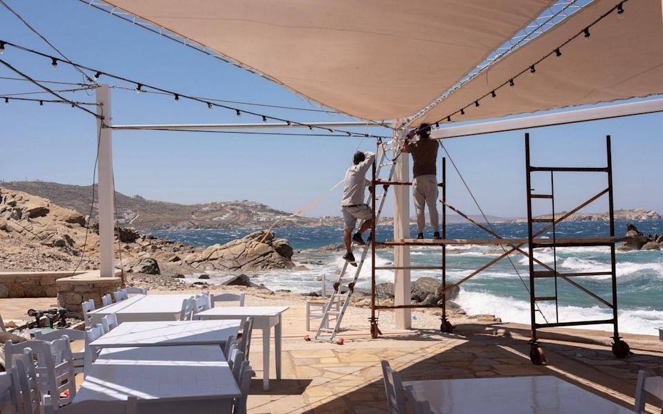 Workers prepare outdoor lighting on the terrace of a taverna - Getty