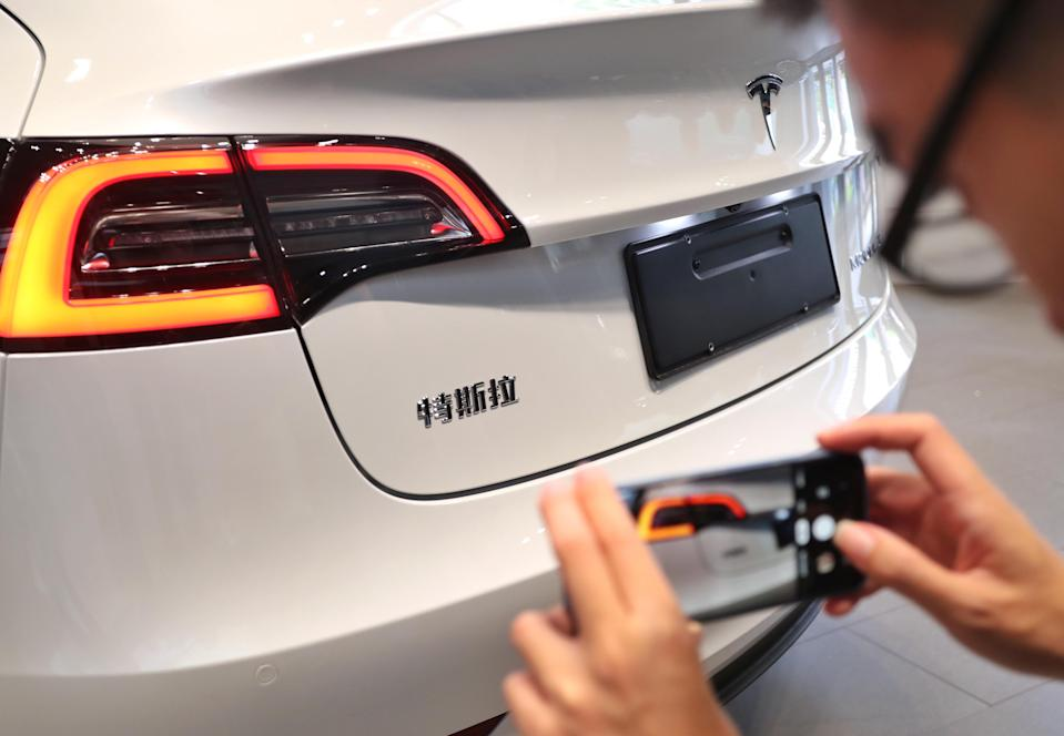 A man takes photos of China-built Tesla Model 3 with its brand name in Chinese characters at a Tesla store on November 22, 2019 in Shanghai, China. China's homegrown