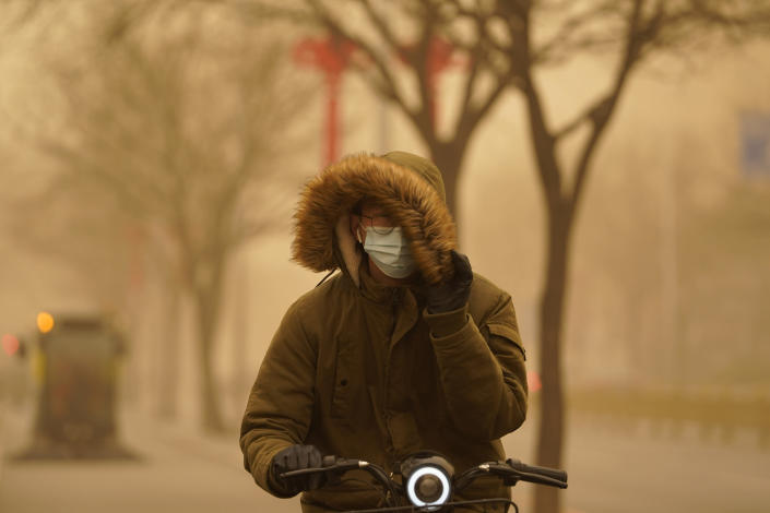 A resident tries to cover his face as he rides through a sandstorm in Beijing, Monday, March 15, 2021. The sandstorm brought a tinted haze to Beijing's skies and sent air quality indices soaring on Monday. (AP Photo/Ng Han Guan)