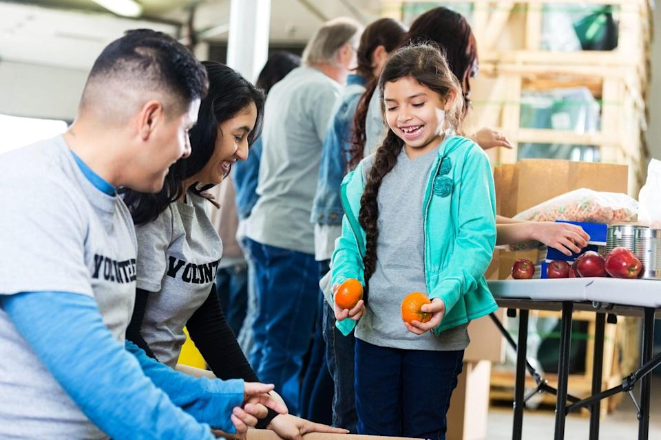 An image of a girl volunteering with her parents in a community food bank.