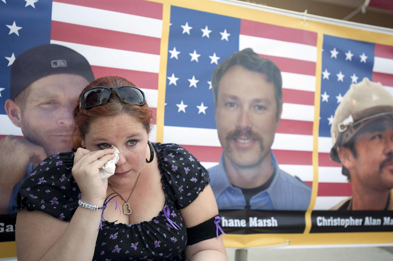 PRESCOTT VALLEY, AZ - JULY 9: Laura Marshall, 29, of Phoenix, Arizona sits in front of a photograph of her cousin, Garret Zuppiger (L) who was one of the 19 firefighters killed in a wildfire, at the entrance to a memorial service in their honor at Tim's Toyota Center July 9, 2013 in Prescott Valley, Arizona. The firefighters, of the Granite Mountain Hotshots crew, died battling the fast-moving blaze on June 30. (Photo by Laura Segall/Getty Images)
