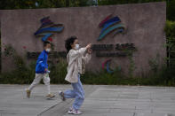 Children wearing masks run past the logos for the Beijing Winter Olympics and Paralympics at the Shougang Park in Beijing Monday, Oct. 4, 2021. When the International Olympic Committee awarded Beijing the 2008 Summer Olympics, it promised the Games could improve human rights and civil liberties in China. (AP Photo/Ng Han Guan)