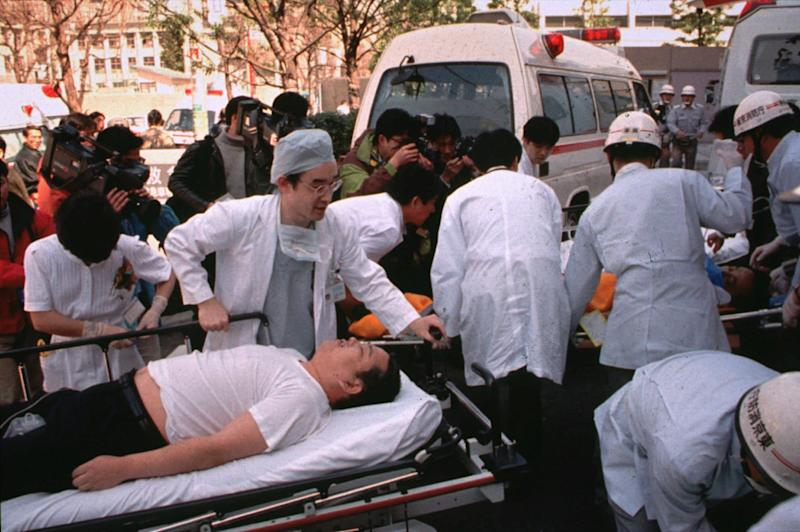 In this March 20, 1995, photo, subway passengers affected by sarin gas planted in central Tokyo subways are carried into St. Luke's International Hospital in Tokyo. (Chikumo Chiaki/AP)