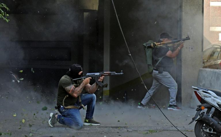 Shiite fighters from the Hezbollah and Amal movements take aim with (L to R) a Kalashnikov assault rifle and a rocket-propelled grenade launcher during the clashes (AFP/IBRAHIM AMRO)