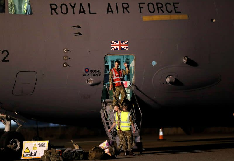 Members of the British armed forces disembark a C-17 aircraft after landing at Brize Norton
