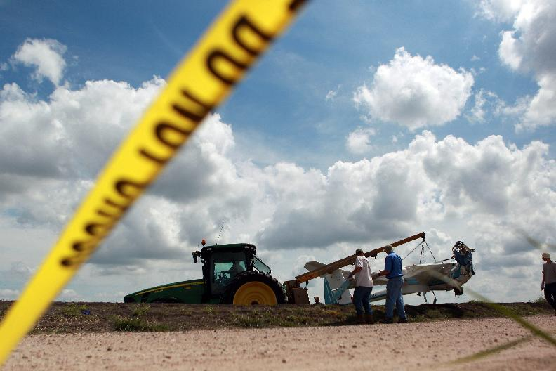 Local first responders, National Transportation Safety Board investigators and a landowner assist in removing a glider that crashed Sunday in a cotton field killing three people including a 3-year-old boy Monday, June 18, 2012, in Wallis, Texas. Authorities are trying to determine what led to the crash that happened at about 5 p.m. near the glider facility at Texas 36 and Cougar Drive Sunday evening. Deputies said Fred Blair, 68, of Wallis, and Matilda Blair, 32, and 3-year-old Andrew Blair of Houston died instantly in the crash. (AP Photo/Houston Chronicle ,Johnny Hanson) MANDATORY CREDIT