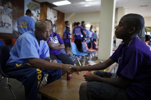 Donte (L), 34, who is serving a two-year sentence, holds the hand of his son Mario, 11, during a visit at San Quentin state prison in San Quentin, California June 8, 2012.