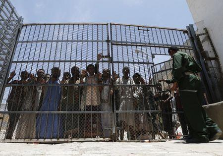 Inmates stand behind gate at central prison in Sanaa