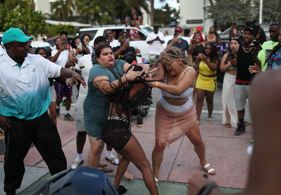 MIAMI BEACH, FLORIDA - MARCH 19: Women fight on the street near Ocean Drive on March 19, 2021 in Miami Beach, Florida. College students have arrived in the South Florida area for the annual spring break ritual. City officials are concerned with large spring break crowds as the coronavirus pandemic continues. Miami Beach police have reported hundreds of arrests and officers' stepped-up deployment to control the spring break crowds. (Photo by Joe Raedle/Getty Images)