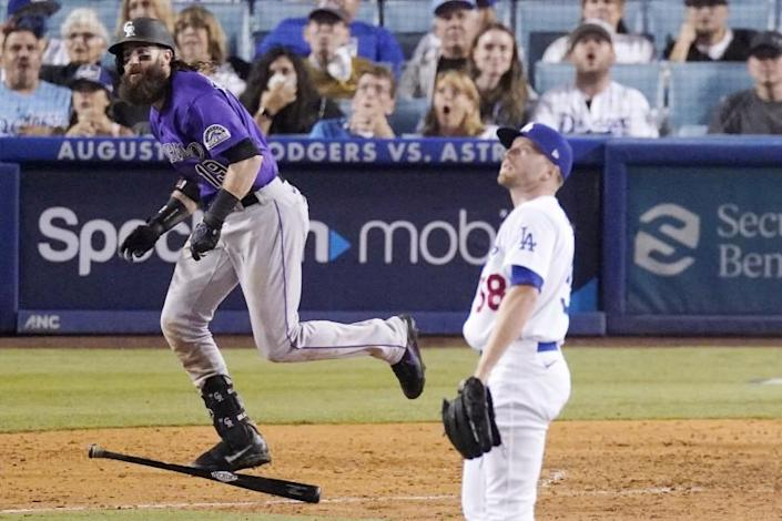 The Rockies' Charlie Blackmon, left, runs after hitting a two-run homer off Dodgers reliever Jimmie Sherfy.