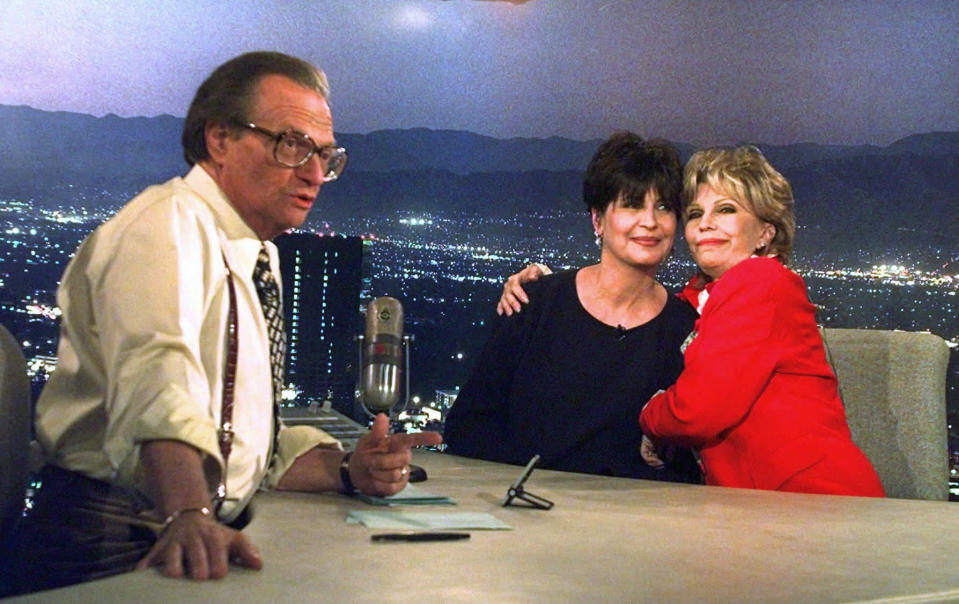 """FILE - In this Dec. 12, 1997 file photo, Tina Sinatra, center, and Nancy Sinatra, right, daughters of the singer Frank Sinatra, joke around on CNN's Los Angeles set of """"Larry King Live"""" as host Larry King makes preparations. King, who interviewed presidents, movie stars and ordinary Joes during a half-century in broadcasting, has died at age 87. Ora Media, the studio and network he co-founded, tweeted that King died Saturday, Jan. 23, 2021 morning at Cedars-Sinai Medical Center in Los Angeles. (AP Photo/Susan Sterner)"""