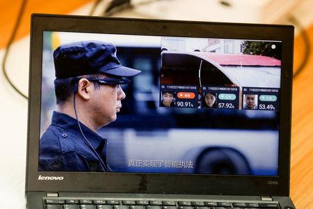 A promotion video shows an actor wearing LLVision facial recognition smart glasses during a demonstration at the company's office in Beijing, China February 28, 2018. Picture taken February 28, 2018. REUTERS/Thomas Peter