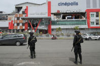 Police officers stand guard to prevent looting at a shopping mall partially damaged by an earthquake in Mamuju, West Sulawesi, Indonesia, Saturday, Jan. 16, 2021. Damaged roads and bridges, power blackouts and lack of heavy equipment on Saturday hampered Indonesia's rescuers after a strong and shallow earthquake left a number of people dead and injured on Sulawesi island. (AP Photo/Sadly Ashari Said)