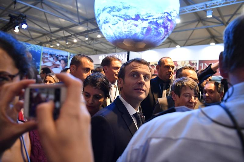 French President Emmanuel Macron (C) has invited heads of state and government, but not President Trump, as well as business leaders, to Paris on December 12 to discuss finance for climate projects (AFP Photo/John MACDOUGALL)