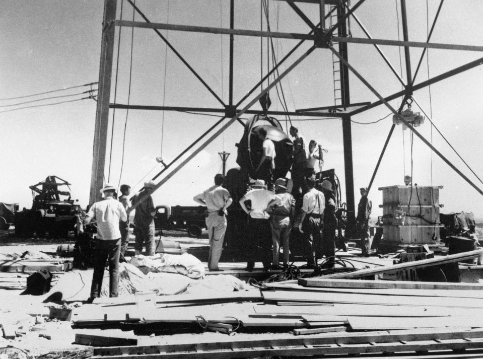 FILE - In this July 6, 1945, file photo, scientists and other workers rig the world's first atomic bomb to raise it up onto a 100 foot tower at the Trinity bomb test site near Alamagordo, N.M. The president of the Navajo Nation and New Mexico residents who live downwind from the site of the world's first atomic blast are among those seeking recognition and compensation from the U.S. government for people affected by uranium mining and nuclear testing carried out during the Cold War. A congressional subcommittee was taking testimony Wednesday, March 24, 2021, about who should be eligible under the Radiation Exposure Compensation Act. (AP Photo/File )