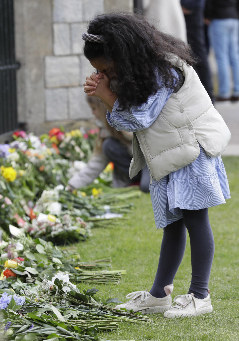 A child prays by the flowers left outside Windsor Castle in Windsor, England Sunday, April 11, 2021. Britain's Prince Philip, the irascible and tough-minded husband of Queen Elizabeth II who spent more than seven decades supporting his wife in a role that mostly defined his life, died on Friday. (AP Photo/Kirsty Wigglesworth)