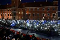 In Warsaw, protesters lit up a central square with their mobile phones, sang the national anthem and chanted 'We're staying!' (AFP/Wojtek Radwanski)