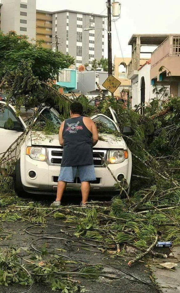 <p>A man removes debris from a car following high winds as Hurricane Irma nears San Juan, Puerto Rico, Sept. 6, 2017, in this image taken from social media. (Photo: Nicole Pellot/Handout via Reuters) </p>
