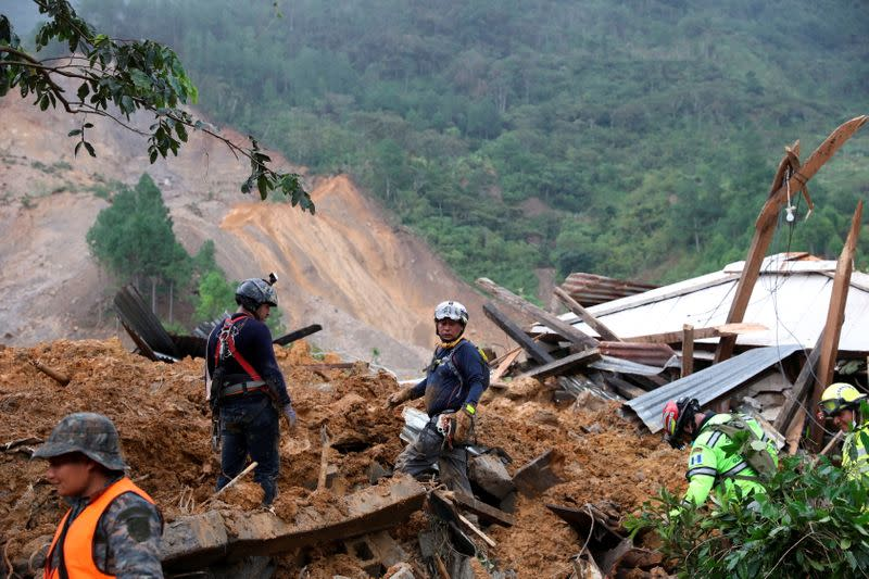 Rescue workers inspect an area hit by a mudslide, caused by heavy rains brought by Storm Eta, as the search for victims continue in the buried village of Queja
