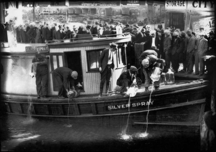 "FILE - In this 1922 file photo spectators gather by the side of captured rum runner, Silver Spray, as they watch prohibition agents pour ""white lightning"" from the five-gallon bottles on the deck into the Elizabeth River, Norfolk, Va. The Prohibition Era, which lasted from Jan. 17, 1920, until December 1933, is now viewed as a failed experiment that glamorized illegal drinking. (Charles S. Borjes/The Virginian-Pilot via AP)"
