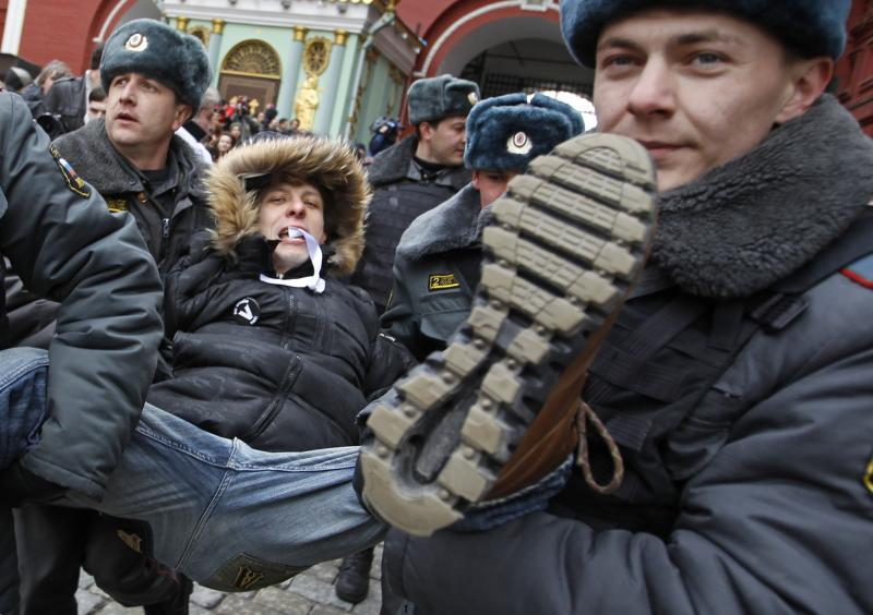 Russian police officers detain a protester during an unsanctioned opposition rally in Moscow, Russia, Sunday, April 1, 2012. Police in Moscow have detained about 30 anti-Kremlin protesters outside the gates to Red Square. Opposition activists called for supporters to walk around Red Square on Sunday wearing the white ribbons that have become a symbol of the protest movement against Prime Minister Vladimir Putin. Putin will begin serving a third presidential term in May. (AP Photo/Mikhail Metzel)