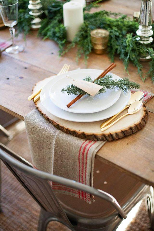 """<p>Create a beautiful base for your Christmas table setting by layering a burlap cloth and wood slice under your dinnerware, and finish the arrangement with a piece of greenery plucked from your centerpiece. </p><p><strong>Get the tutorial at <a href=""""http://www.laurenmcbrideblog.com/2016/11/farmhouse-christmas-tablescape/"""" rel=""""nofollow noopener"""" target=""""_blank"""" data-ylk=""""slk:Lauren McBride"""" class=""""link rapid-noclick-resp"""">Lauren McBride</a>.</strong></p><p><strong><a href=""""https://www.amazon.com/Walnut-Hollow-41803-Basswood-Weddings/dp/B01LWML3JD/"""" rel=""""nofollow noopener"""" target=""""_blank"""" data-ylk=""""slk:SHOP WOOD SLICES"""" class=""""link rapid-noclick-resp"""">SHOP WOOD SLICES</a><br></strong></p>"""