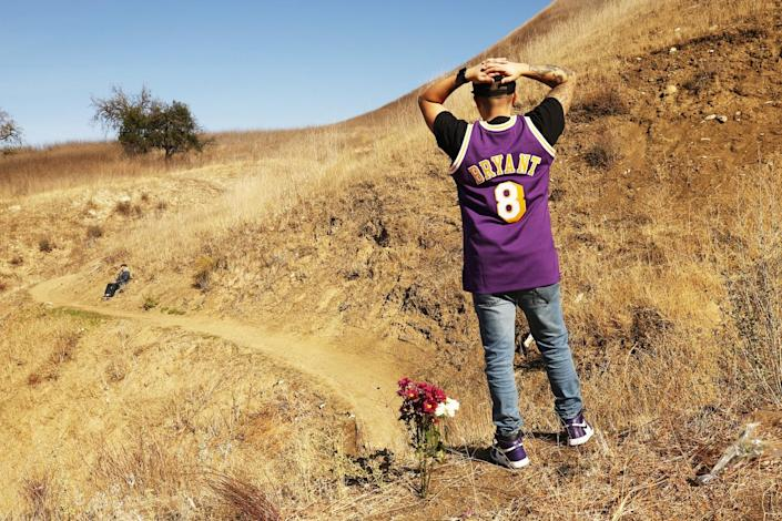 Anthony Calderon raises his arms in silence on the mountainside in Calabasas.