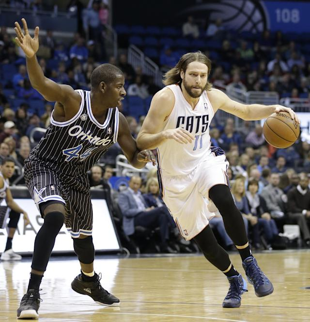 Charlotte Bobcats' Josh McRoberts (11) drives around Orlando Magic's Andrew Nicholson (44) during the first half of an NBA basketball game in Orlando, Fla., Friday, Jan. 17, 2014. (AP Photo/John Raoux)