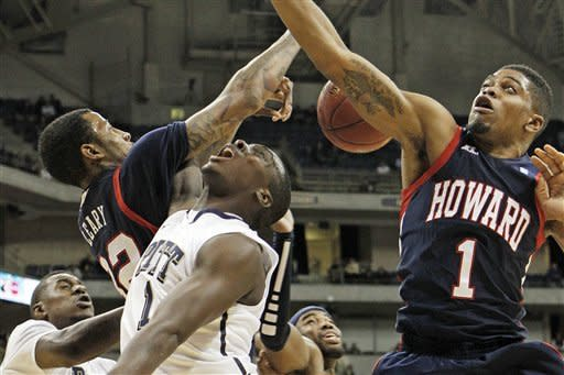 Pittsburgh's Tray Woodall (1) is fouled as he shoots between Howard's Alphonso Leary (32) and Tre Lee (1) during the first half of an NCAA college basketball game Tuesday, Nov. 27, 2012, in Pittsburgh. (AP Photo/Keith Srakocic)