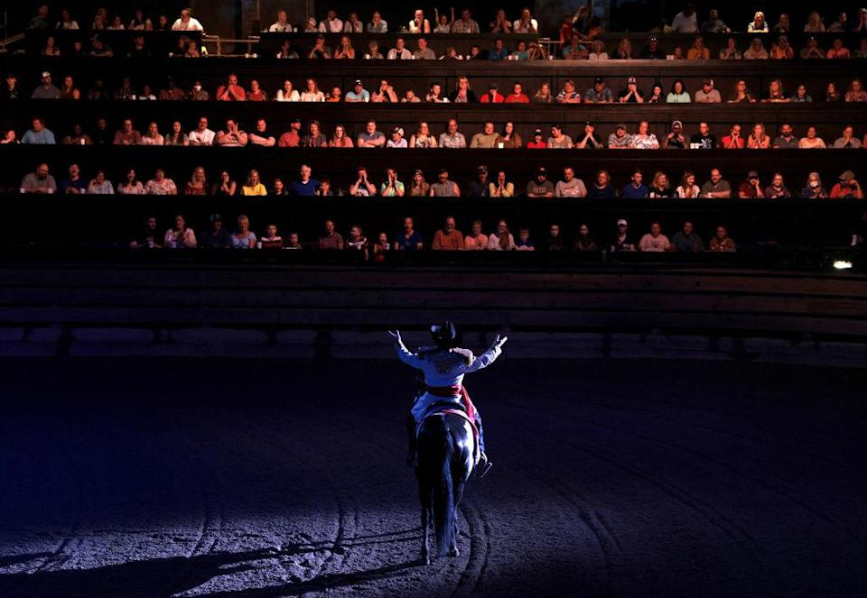 """A performer spreads his arms out to those seated in The South as he divides the room of diners at Dolly Parton's Stampede into factions of North and South which will cheer on their teams as they compete in various events like barrel riding, chicken chasing, and pig races in Branson, Mo. on July 17, 2021.<span class=""""copyright"""">Jessica Rinaldi—The Boston Globe/Getty Images</span>"""