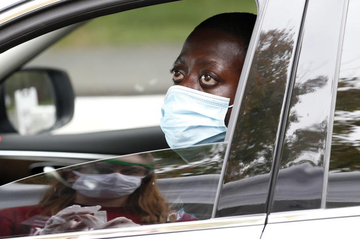 AMHERST, MA - SEPTEMBER 9: Clement Boaheng, 24, a first year Graduate Student in Public Health at UMass Amherst talks with nursing student Claire Sullivan after he gave her his self administered COVID-19 test at a drive through coronavirus testing site on campus in Amherst, MA on Sept. 9, 2020. (Photo by Jessica Rinaldi/The Boston Globe via Getty Images)