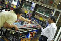 Workers at Stern Pinball assemble an Iron Man machine in Chicago on August 15, 2011. Each machine uses over a half a mile of wire and it takes more than 30 hours to assemble the 3,500 or so parts