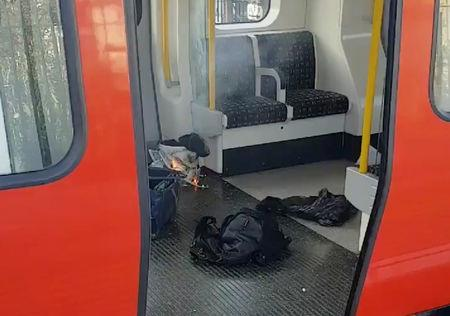 Personal belongings and a bucket with an item on fire inside it, are seen on the floor of an underground train carriage at Parsons Green station in London