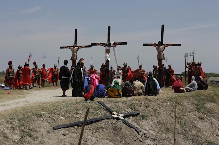 Filipino devotee Ruben Enaje, center, stays nailed to a cross with two actors during a play to re-enact the crucifixion of Jesus Christ in San Pedro Cutud village, Pampanga province, northern Philippines on Friday, April 18, 2014. Church leaders and health officials have spoken against the practice which mixes Roman Catholic devotion with folk belief, but the annual rites continue to draw participants and huge crowds. (AP Photo/Aaron Favila)
