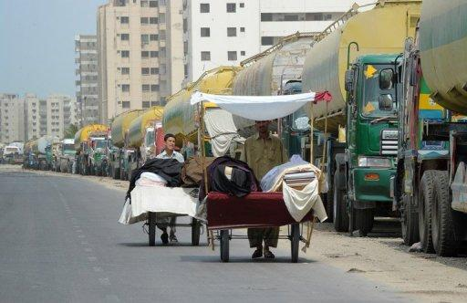Street vendors selling clothing material push their carts past oil tanker trucks parked on the side of a road in Karachi on July 12. Pakistan on Tuesday signed a deal with the United States governing arrangements for NATO convoys travelling to Afghanistan, seeking to draw a line under a seven-month border blockade