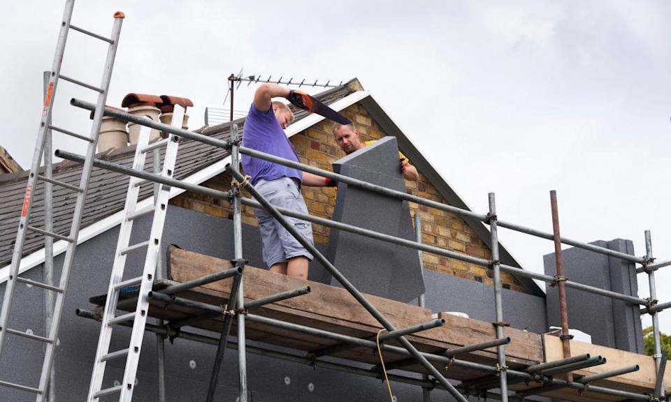 Builders attach rigid foam wall insulation sheets on a Victorian terraced house.