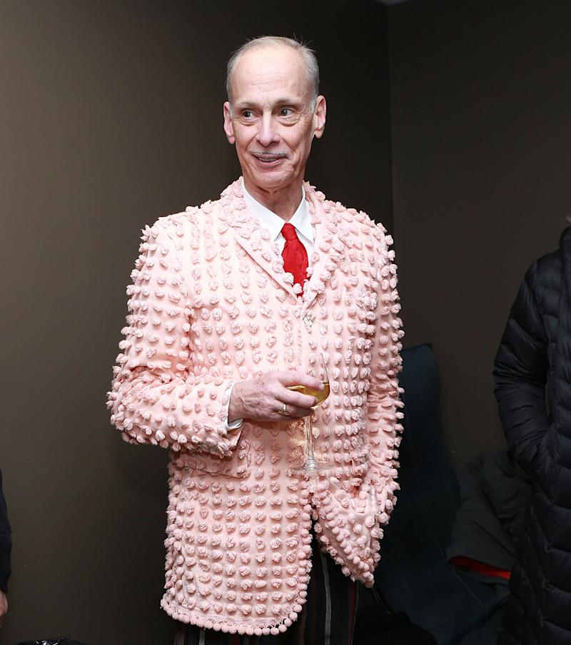 """John Waters is often called the """"King of Camp,"""" both because of his taste for strange suits &mdash; hence this pink number, which might have been yanked from your grandmother's bedspread &mdash; and his love of """"freaks."""" He even hosted a camp once. <a href=""""https://www.nytimes.com/2017/10/14/style/john-waters-camp.html"""" target=""""_blank"""" rel=""""noopener noreferrer"""">An actual sleep-away camp.</a>&nbsp;(Anyway, weird suits are the way to go. It's the only opportunity you have.)"""