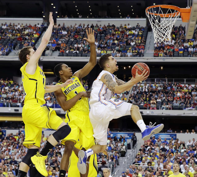 Florida's Scottie Wilbekin, right, shoots as Michigan's Glenn Robinson III (1) and Nik Stauskas (11) defend during the first half of a regional final game in the NCAA college basketball tournament, Sunday, March 31, 2013, in Arlington, Texas. (AP Photo/David J. Phillip)