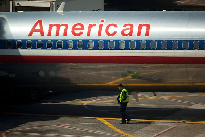 An airport worker walks past an American Airlines Inc. plane standing at a gate at LaGuardia Airport in the Queens borough of New York, U.S., on Monday, April 25, 2011. American Airlines Inc. is trying to grab market share in New York, the biggest and possibly most-contested U.S. aviation market, with terminal upgrades at LaGuardia Airport. Delta Air Lines Inc.'s bid to redo its space remains in limbo, bogged down in talks with federal regulators and US Airways Group Inc. about access to more landing rights. Photographer: Michael Nagle/Bloomberg (Bloomberg)