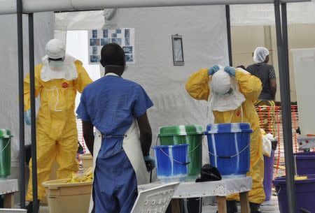 A Doctors Without Borders health worker takes off his protective gear under the surveillance of a colleague at a treatment facility for Ebola victims in Monrovia