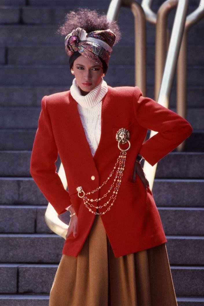 <p>A model poses in a red chained blazer and head scarf. </p>