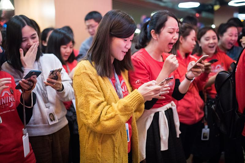 HANGZHOU, CHINA - NOVEMBER 12: Alibaba employees look at their cellphones during celebrations at Alibaba's Xixi base after Alibaba Group's 11.11 Global Shopping Festival on November 12, 2018 in Hangzhou, Zhejiang Province of China. The gross merchandise volume (GMV) of 2018 Alibaba Group's 11.11 Global Shopping Festival surpassed 213.5 billion yuan (about 30.7 billion US dollars) on Sunday. (Photo by VCG/VCG via Getty Images)